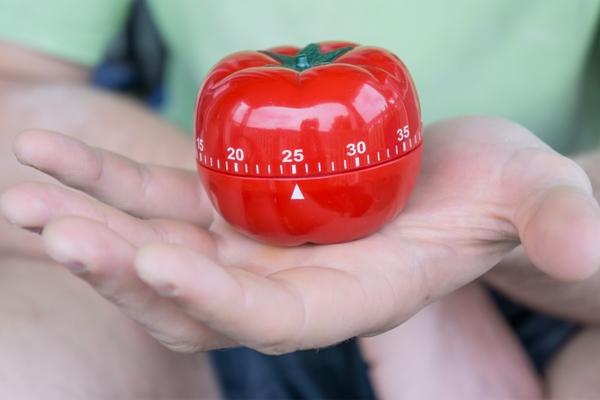 Minuteur en forme de tomate dans une main